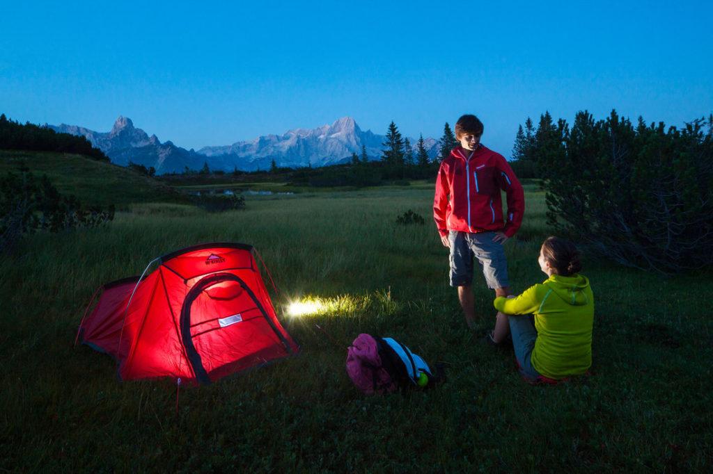 Bergwanderung in den Bergen oberhalb von Filzmoos vor der Kulisse der Bischofsmütze, Gosaukamm, Dachstein, an einem Bergsee (Moorsee) ein Zelt für die Nacht aufgestellt und genießen die blaue Stunde in der herrlichen Bergwelt